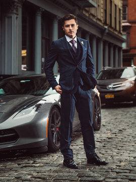 Young successful entrepreneur man standing near sport luxury car wearing a classic suit