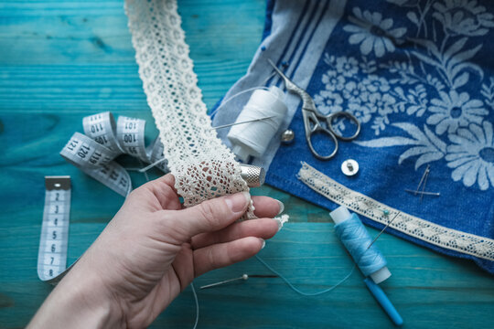 close up of hand in thimble holding lace