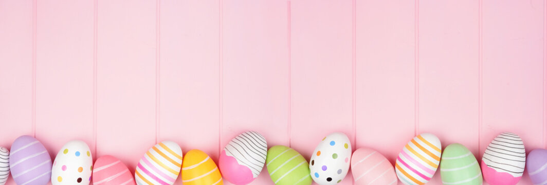 Colorful Easter Egg bottom border over a soft pink wood banner background. Top down view with copy space.