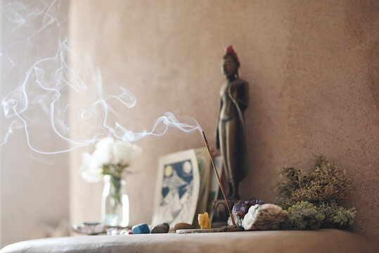Altar with stones and incense in adobe house interior