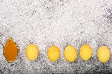 Coloring Easter Eggs from natural turmeric powder in yellow color. Easter chicken eggs on a...