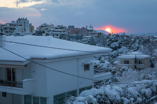 A beautiful winter evening before sunset panoramic view of the snow-covered roofs and streets of Athens city-Greece.