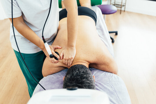 Patient lying on the stretcher in the physiotherapy clinic is treated with diathermy treatment for muscle pain. Rehabilitation of a sick patient with muscle pain. Health concept