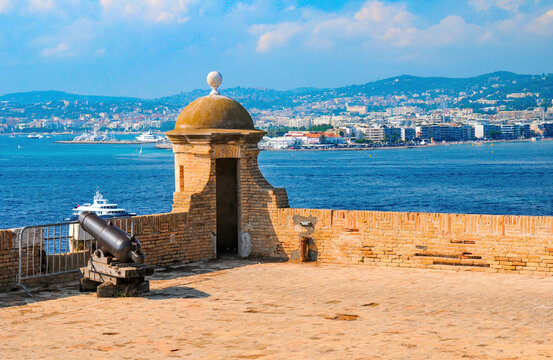 Tower and cannon of Fort Royal on Sainte-Marguerite Island. Cannes in opposite shore. Lerins Islands, France