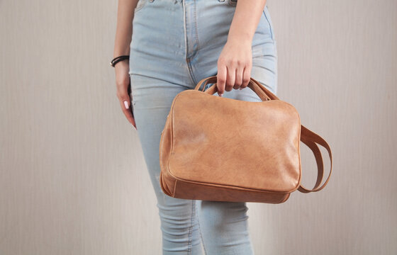 Caucasian woman with a brown bag at home.