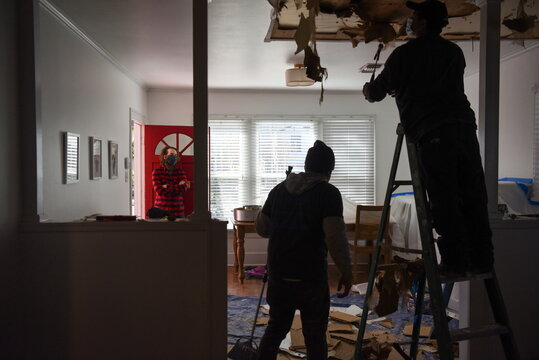 Drew Ainscough looks on as contractors remove material from the ceiling of his recently-purchased home in Houston