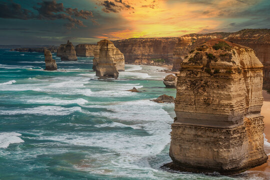 Blue green ocean and beach with sandbanks cliffs and waves  with close view of The twelve apostles and cliffs in the shadow of the sunset  in Victoria, Australia against a orange cloudy sky