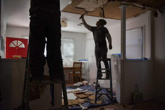 Contractors remove material from a ceiling in a recently-purchased home in Houston
