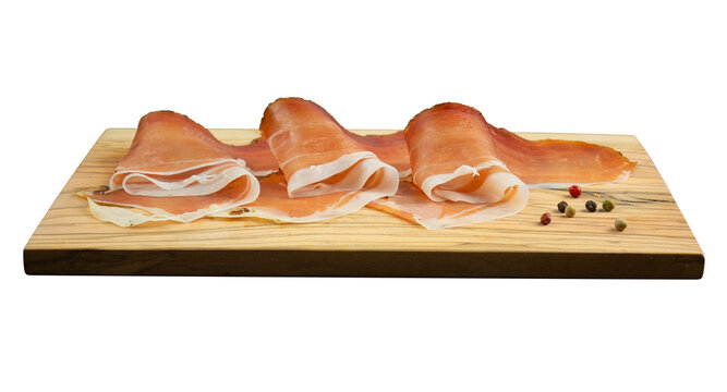 Slices of speck ham on wooden cutting board isolated on white