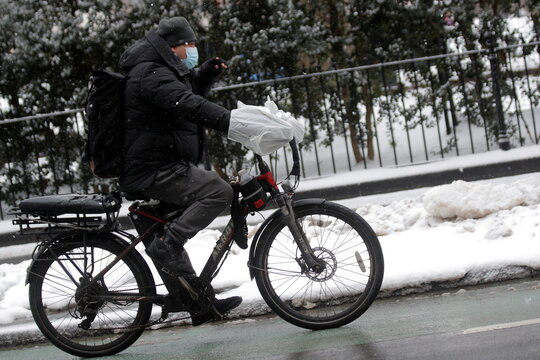 A food delivery person rides an electric bike during a snow storm in New York