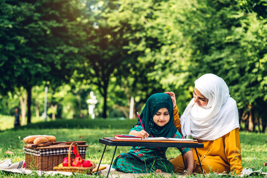 Portrait of happy religious enjoy happy love asian family arabic muslim mother and little muslim girls child with hijab dress smiling and having fun moments good time in summer park