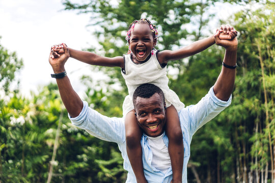 Portrait of enjoy happy love black family african american father carrying daughter little african girl child smiling and having fun moments good time in summer park at home