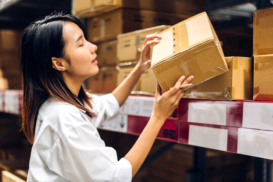 Portrait of smiling asian manager worker woman standing and order details on cardboard box for checking goods and supplies on shelves with goods background in warehouse.logistic and business export