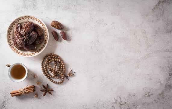 Ramadan food and drinks concept. Ramadan wood rosary, tea, and dates fruits on dark background.
