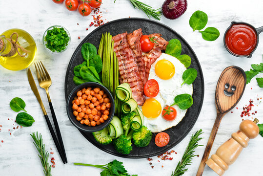 English breakfast: chickpeas, avocados, scrambled eggs, bacon vegetables on a black stone plate. Top view. Free space for text.