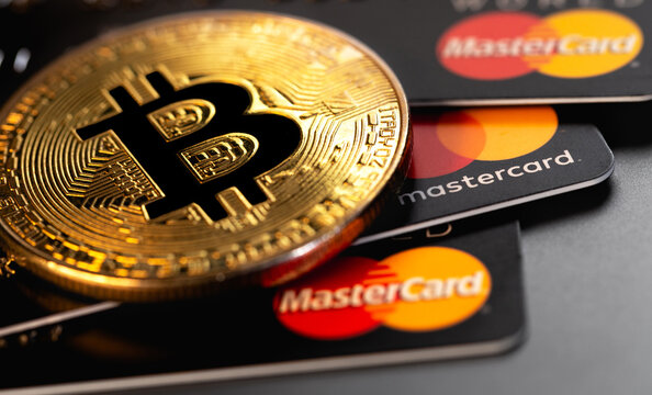 bitcoin cryptocurrency with MasterCard plastic electronic cards closeup. MasterCard worldwide is an American multinational financial services corporation. Moscow, Russia - January 18, 2021