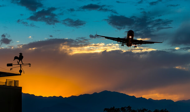 Landing airplane above colorful clouds and weather vane on the end of building