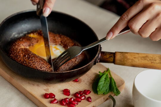 Turkish breakfast, scrambled eggs in a simit bun in a frying pan, coffee in a Turk, fresh bread