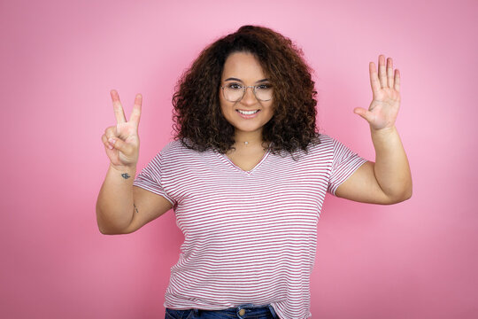 Young african american woman wearing red stripes t-shirt over pink background showing and pointing up with fingers number seven while smiling confident and happy