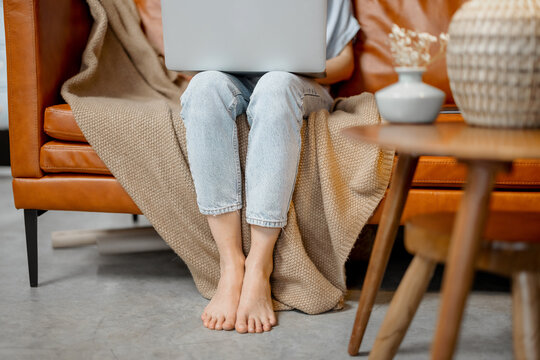 Woman's legs on the floor while she working with laptop and sitting on sofa. . High quality photo