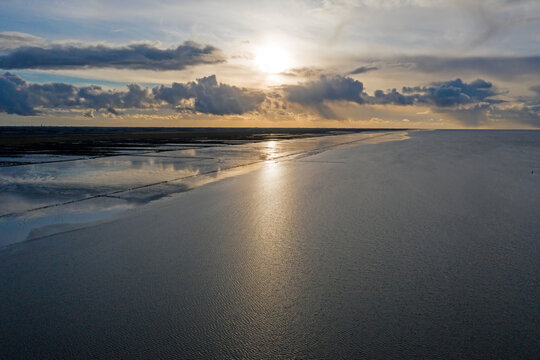 Aerial from the coast line at the Wadden Sea near Holwerd in the Netherlands at sunset