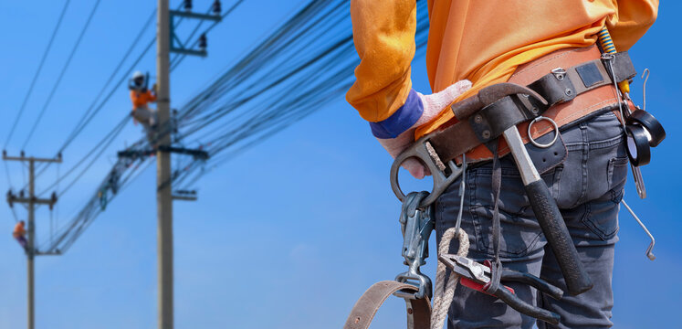 Rear view of electrician with safety belt and work tools is preparing to work on high altitude with blurred background of electrical workers team are working on power poles against blue sky
