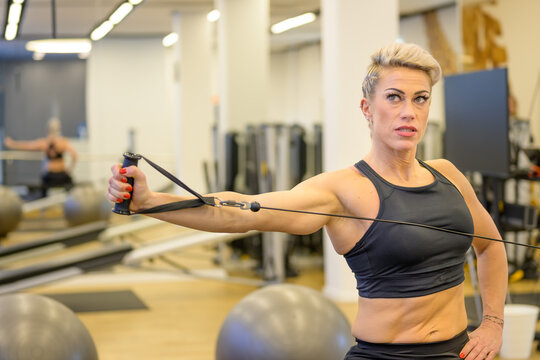 Sporty middle-aged woman working out with stretch bands
