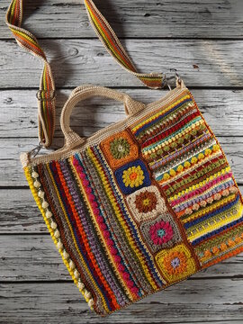 Image of colorful crochet bag made of leftover yarn. Isolated against white rustic wooden surface. Concept of creativity, something bright colorful, and utilization leftover things.