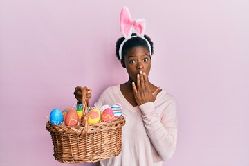 Young african american girl wearing cute easter bunny ears holding basket with painted eggs covering mouth with hand, shocked and afraid for mistake. surprised expression