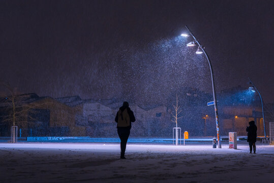 Snow flurries on a square in the evening, street lights and snow flurries, it snows in the evening on a large, illuminated square, one walking person
