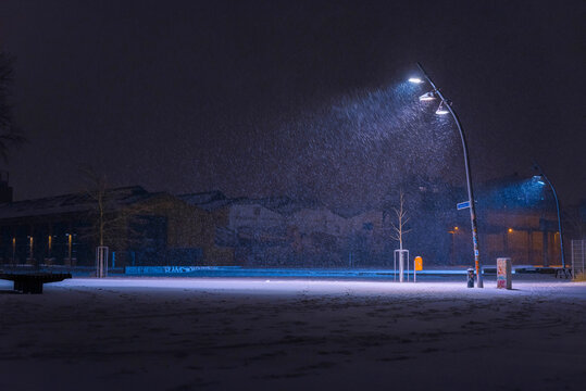 Snow flurries on a square in the evening, street lights and snow flurries, it snows in the evening on a large, illuminated square