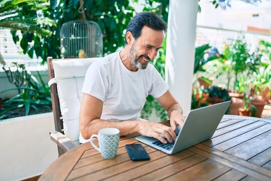 Middle age man with beard smiling happy at the terrace working from home using laptop