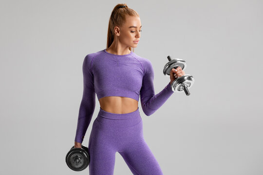 Fitness woman working out with dumbbells on gray background. Athletic girl doing exercise