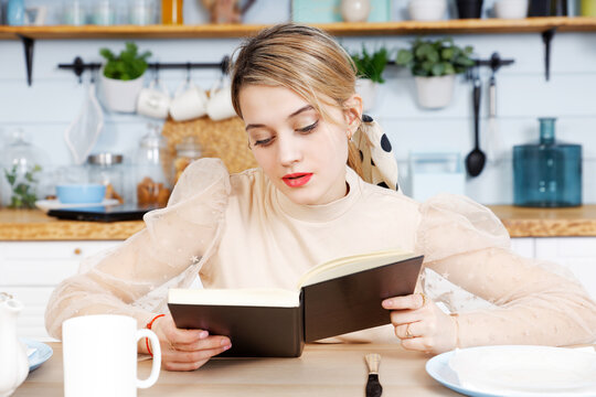 Young pretty woman reading book in the kitchen against blurred background.