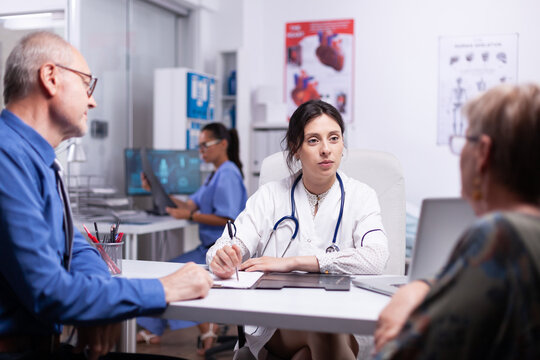 Young doctor consulting elderly couple sitting in medical office, while medical nurse working in background. Practitioner asking questions to mature patients filling disease history form, prescribing