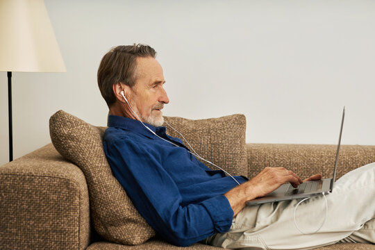 Side view of a handsome senior man lying on sofa typing on laptop