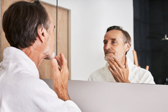 Senior man touching his chin in bathroom in front of a mirror