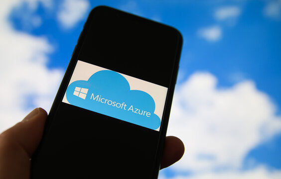 Viersen, Germany - February 9. 2021: Closeup of smartphone with logo lettering of cloud computing provider service microsoft azure, blurred sky and cloud background