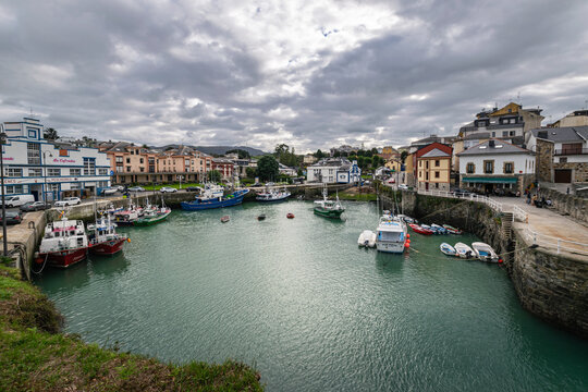 Picturesque port area of Puerto de Vega town in Asturias, Spain with beautiful blue waters and fishing boats.