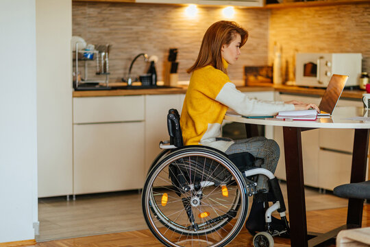 Female in wheelchair using laptop at home