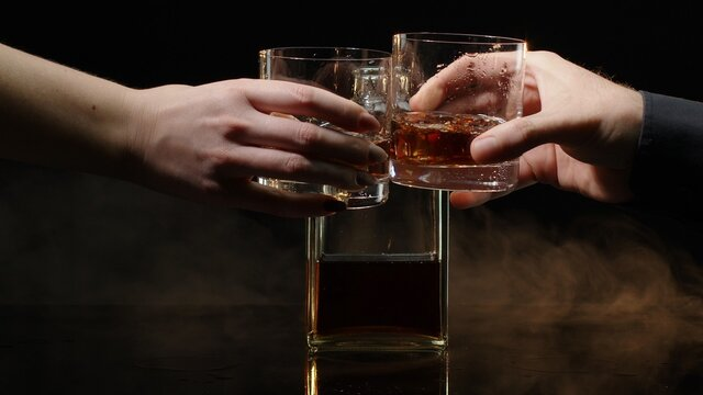 Two hands with glasses of cognac whiskey with ice cubes making cheers on black background. Celebration of business success, Christmas, anniversary, birthday. Raising toast with glasses of bourbon, rum