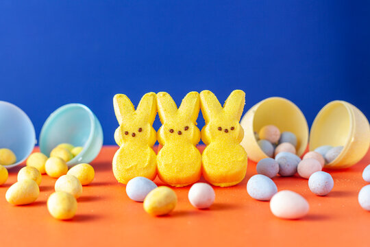 Easter holiday celebration concept with three little marshmallow bunnies and multiple small colorful crisp sugar coated chocolate easter eggs on orange surface with yellow background. Versatile image.