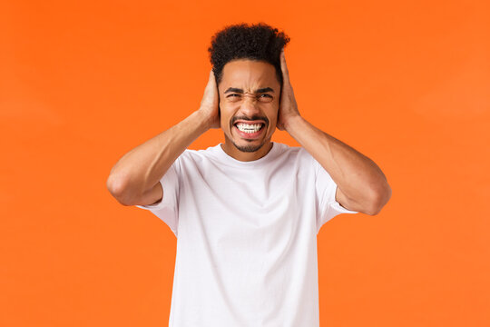 Unsatisfied african-american guy feeling discomfort and headache, clench teeth bothered, look up and cover ears hearing unsatisfying loud noise, distressed by neighbours, orange background