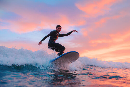 Young surfer boy, surfing at sunset on a Portuguese beach. Copy Space