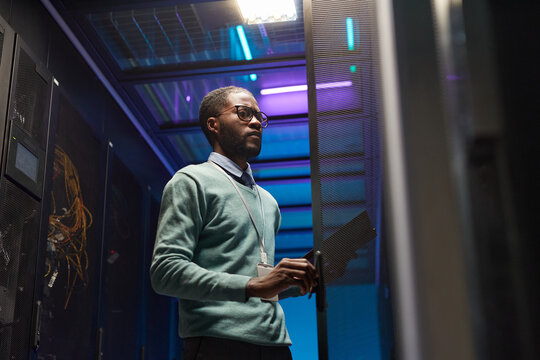 Low angle view at African American data engineer working with supercomputer in server room lit by blue light, copy space