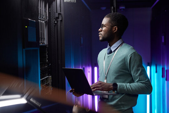 Side view portrait of African American data engineer holding laptop while working with supercomputer in server room lit by blue light, copy space