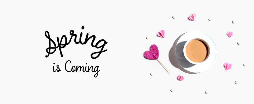 Spring is coming message with a cup of coffee and paper hearts - flat lay