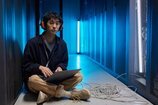 Full length portrait of young Asian man sitting on floor in server room lit by blue light while setting up supercomputer network, copy space