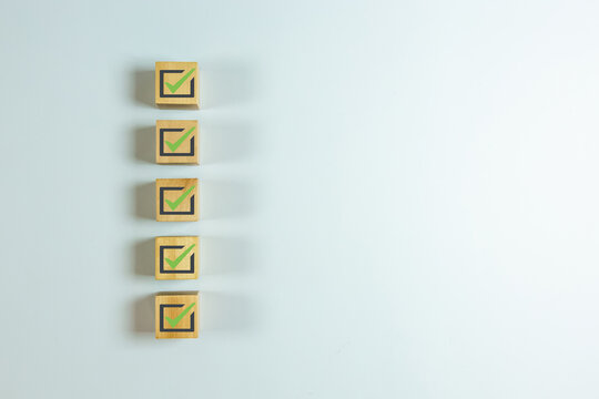 Wood cube with check mark on white background, Checklist concept, Copy space.