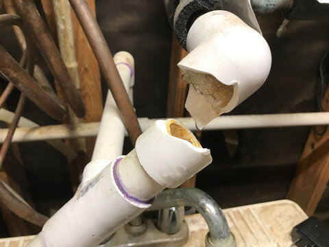 Busted plumbing PVC water pipe with ice frozen and water dripping